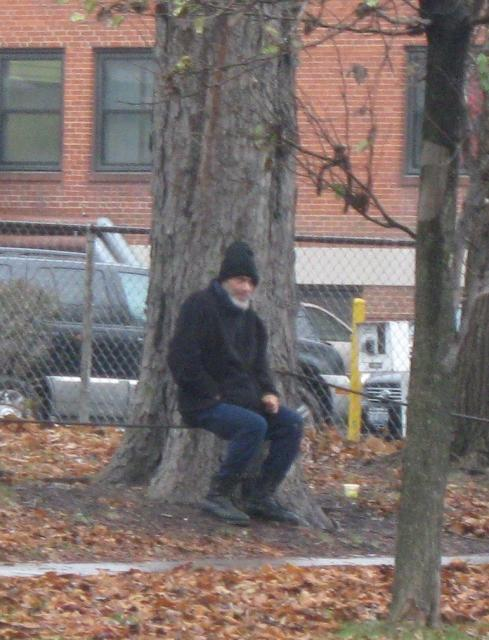 FRANK GIGLIO SITTING BENEATH A TREE IN THE DRIZZLILNG RAIN AS HIS HOUSE IS BROUGHT TO THE GROUND